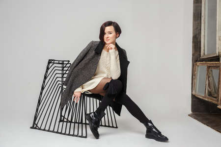 short haircut: Young woman with short haircut posing on black metal chair over grey background. Stock Photo