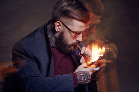 smoking a cigar: Bearded fashionable man smoking a cigar.