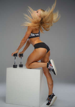 sexy blonde girl: Blond fitness woman posing with dumbells over grey background.