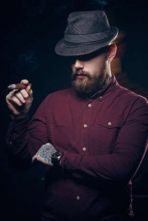 Bearded fashionable man smoking a cigar.