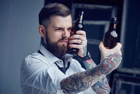 botle: Bearded tattooed man holding beer bottles.