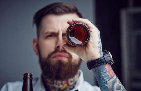 monocular: Bearded tattooed man holding beer bottle like monocular. Stock Photo