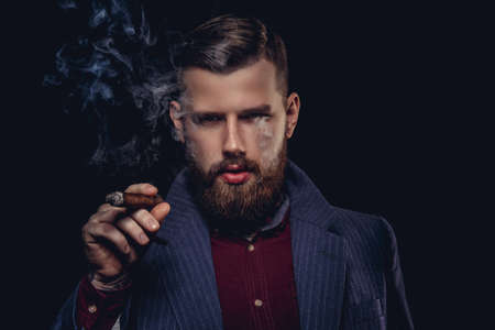 Serious bearded man in a suit smoking cigar.