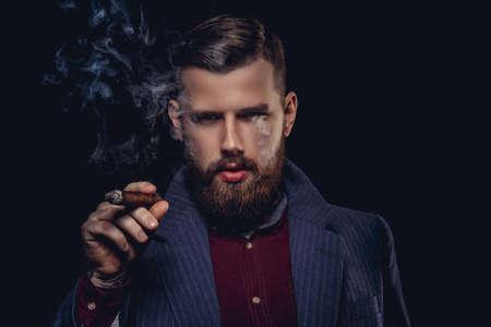 Seus bebaarde man in een pak rokende sigaar.