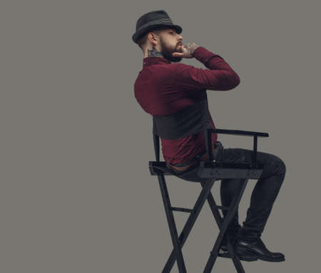 cinematographer: Man in hat sitting on film directors chair. Isolated on grey background. Stock Photo