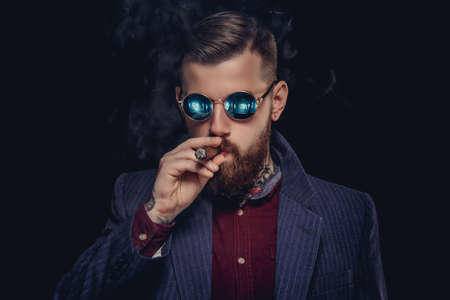 Bearded guy in sunglasses smocking cigar.