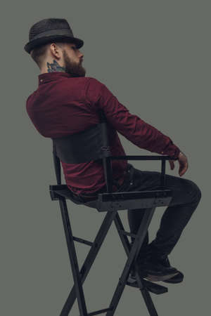 filmmaker: Man in hat sitting on film directors chair. Isolated on grey background. Stock Photo
