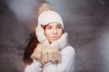 female christmas: A girl in warm sweater, hat and gloves near her face. Stock Photo