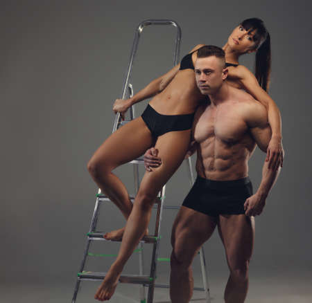 beautiful feet: Shirtless bodybuilder and athletic brunette woman in underwear standing on iron ladder. Isolated on grey background. Stock Photo