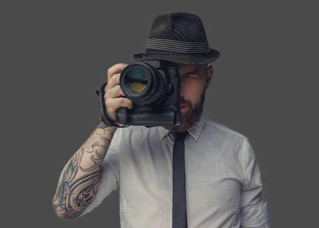 Digitale fotograaf in wit overhemd en casual hoed. Geïsoleerd op grijze achtergrond. Stockfoto