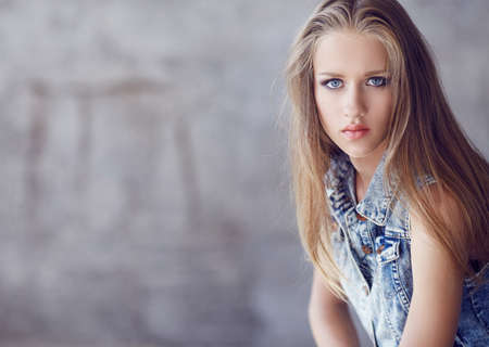 denim jacket: Blue eyes woman with long blond hair in denim jacket. Stock Photo