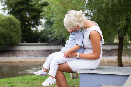 colum: Blond woman with a child on her knees in a park. Stock Photo