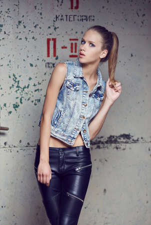 leather pants: Blue eyes young woman in denim jacket and leather pants posing on camera. Stock Photo