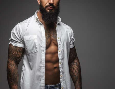 회색 배경에 고립 된 흰 셔츠에 수염 난된 근육 남자. 스톡 콘텐츠
