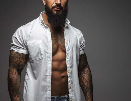Bearded muscular man in a white shirt isolated on a grey background. Foto de archivo