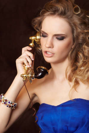 blue dress: A young woman with blond curly hair in a blue dress holds an antique handset. Stock Photo
