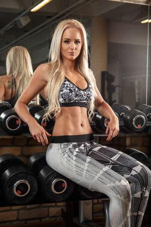 fitness mujer delgada rubia en ropa deportiva gris sentado en pesas de pie.