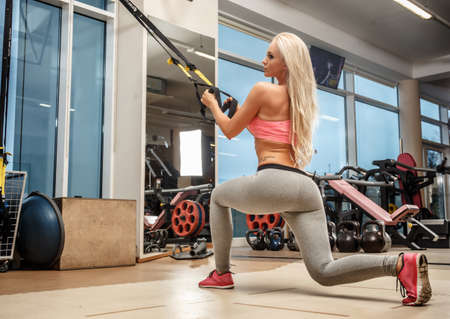 expander: A blond sporty woman doing exercises with expander in a gym.