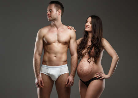 Topless pregnant woman posing with her naked husband.