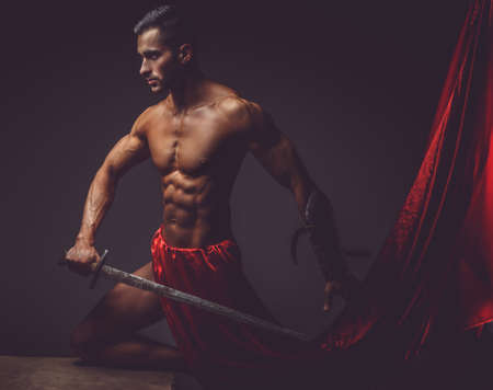 gladius: Muscular man ancient Rome soldier holding a sword dressed in a red fluttering dress.