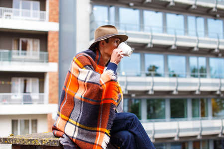 interactivity: A man coverd with blanket drinking hot tea. Stock Photo