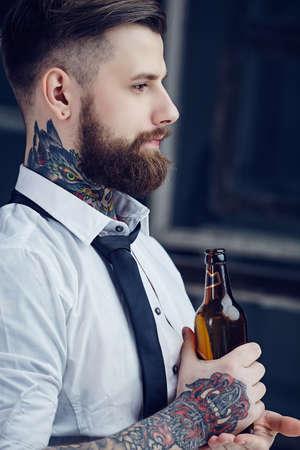 homme barbu avec des tatouages ??sur son bras dans une bière chemise potable blanc.
