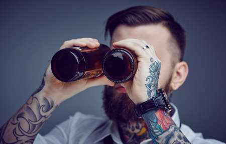 bad hair: Bearded tattooed man looking through beer bootles. Stock Photo