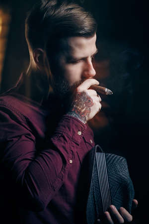 smoking a cigar: A man with tattoo on his arm smoking a cigar.