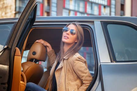 Casual young woman in sunglasses sits on a cars back seat.