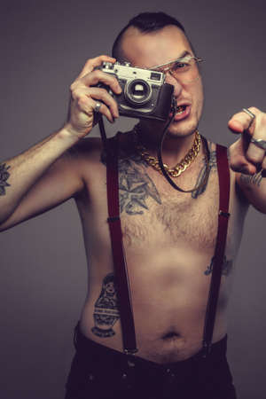 creativ: Creativ man with tattooes on his body holds slr camera.