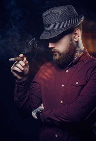 Un hombre con barba en un sombrero fumar un cigarro.