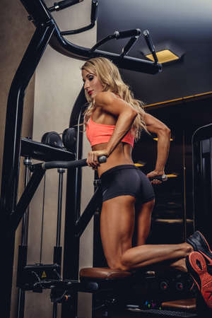exercise machine: Sexy blond fitness woman doing exercises on exercise machine.