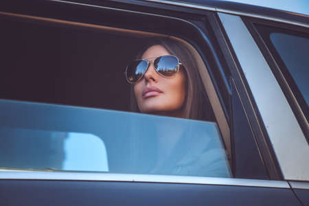 A woman in sunglasses looking through cars window.