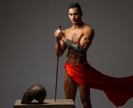 guerrero: Muscular hombre antiguo soldado que sostiene una espada de Roma con un vestido que agita roja.