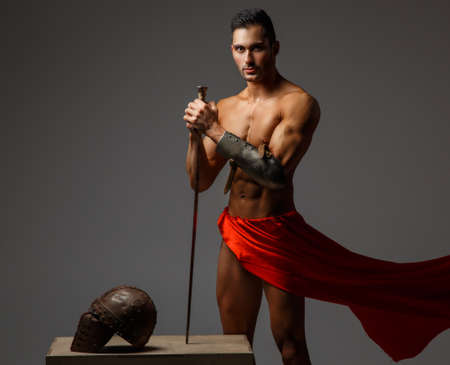 Muscular man ancient Rome soldier holding a sword dressed in a red fluttering dress.