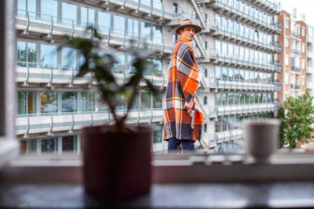 interactivity: A man covered with blanket standing against city building.