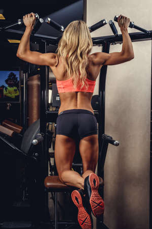 lats: Sporty blond woman doing lats exercises in a gym.