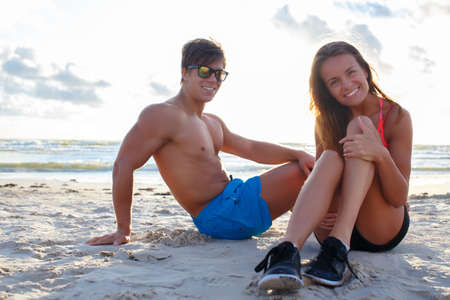 cute guy: Smiling muscular guy in sunglasses and sporty cute woman sitting on the beach.