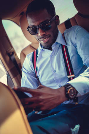 A black man in sunglasses sitting in the car and chatting with smartphone.