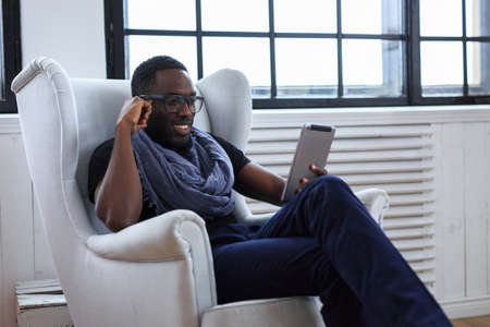 Blackman in eyeglasses working with table pc. Stock Photo