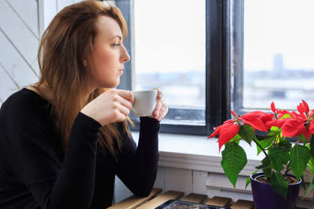 looking through window: Young woman drinks coffee and looking through window.