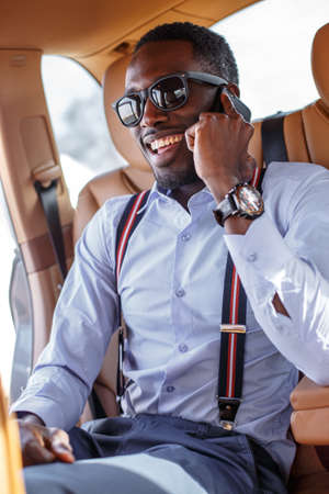 Smiling blackman in the car speaking on smartphone. Stock Photo