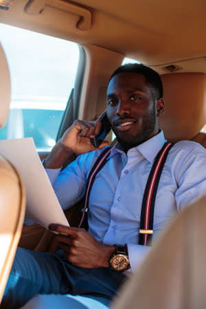back seat: Blackman in a blue shirt sits on cars back seat. Stock Photo