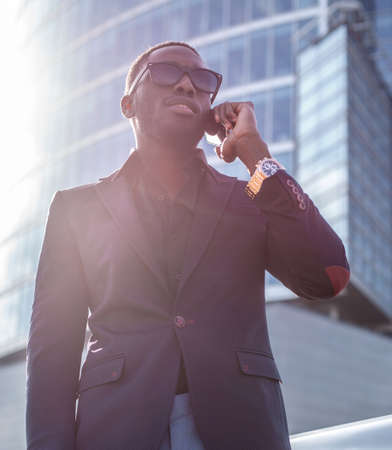 blackman: Modern blackman in a suit speaking on smartphone. Stock Photo