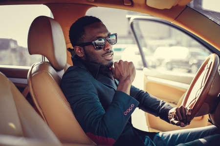 Blackman in zonnebril rijden een auto. Stockfoto