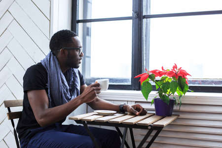 blackman: African american man drinking coffee at the table.