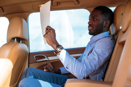Blackman in a blue shirt sits on cars back seat. Stock Photo