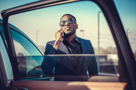 blackman: African american businessman in a suit speaking on smartphone.