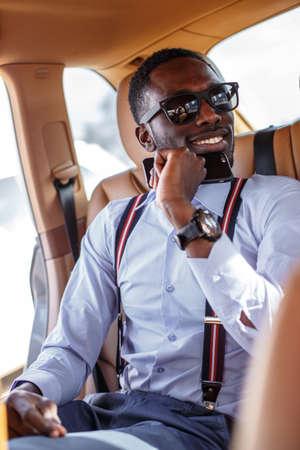 blackman: Modern blackman in a blue shirt sits on cars back seat.
