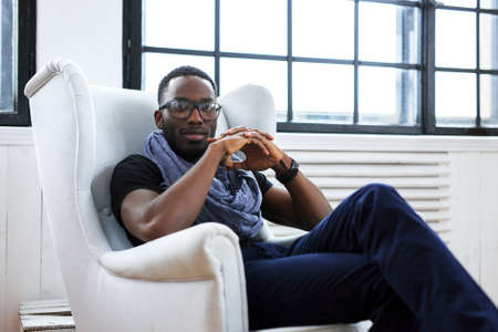 African american man sits on a white chair.